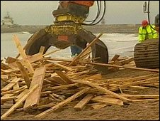 Contractors removing timber from beach