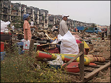 Residents stand amid rubble
