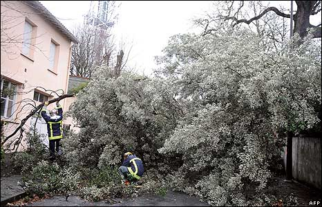 Firemen clear a street covered in broken branches in Toulouse, France