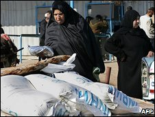 Palestinian woman collects food aid