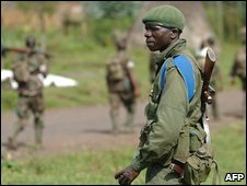 Congolese soldier watches as Rwandan troops pass on road east of Goma