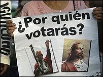 Mujer con un cartel con la imagen de Morales y de Jesucristo