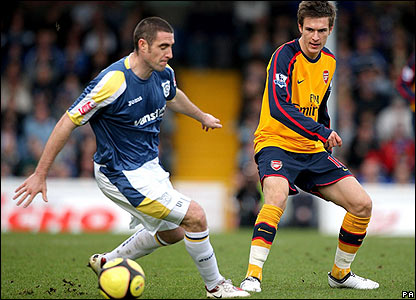 Mark Kennedy shields the ball from former Cardiff star Aaron Ramsey
