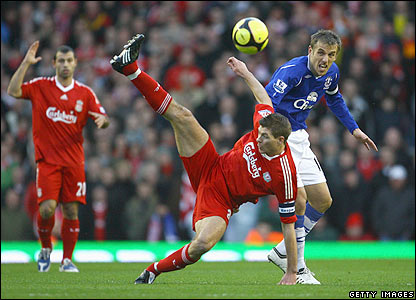 Reds skipper Steven Gerrard is upended by Phil Neville