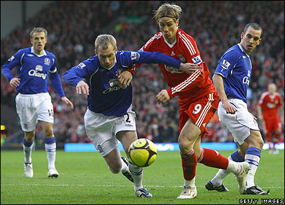 Everton's Tony Hibbert battles for the ball with Fernando Torres