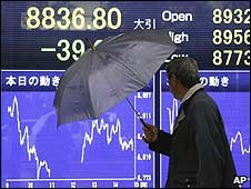 A man walks past a stock market board in Tokyo, Japan (09/01/2009)
