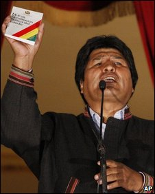 Bolivian President Evo Morales holds aloft a copy of the new constitution