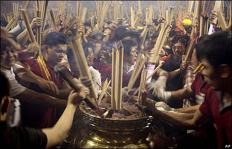 Buddhists rush to place incense sticks in an urn at a Chinese Buddhist temple in Singapore