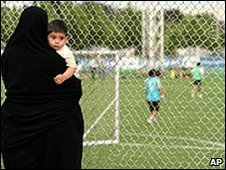 Iranian woman watches football from behind a fence