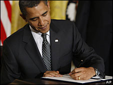 Barack Obama signs an executive order after speaking to the media about green energy and fuel emissions