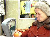 Женщина выбирает мандарины в магазине