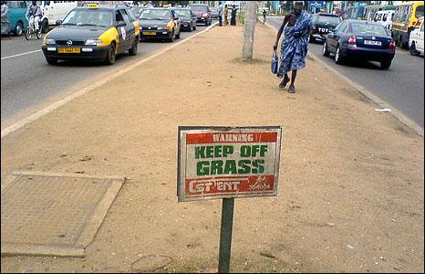 "A sign on a dirt pavement reading,  ""Keep off the grass""  (Photo: BBC News website reader Arthur Buliva)"