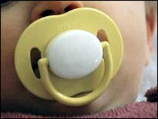 A baby sucks on a dummy