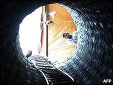 Palestinian men look down a smuggling tunnel near the Gaza border with Egypt, file pic from January 2009