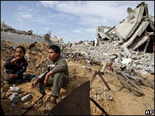 Two boys sit in the ruins of their home in Jabaliya, Gaza, on 27 January 2009