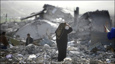 A Palestinian woman stands in the rubble of destroyed houses in Jabaliya, northern Gaza Strip