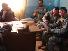 American military policemen discussing local crime with Iraqi police
