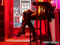 A prostitute sits in the window of her room in Amsterdam's red light district