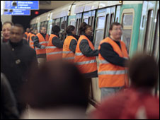 Paris metro employees help to close the doors of a metro on 29 January 2009