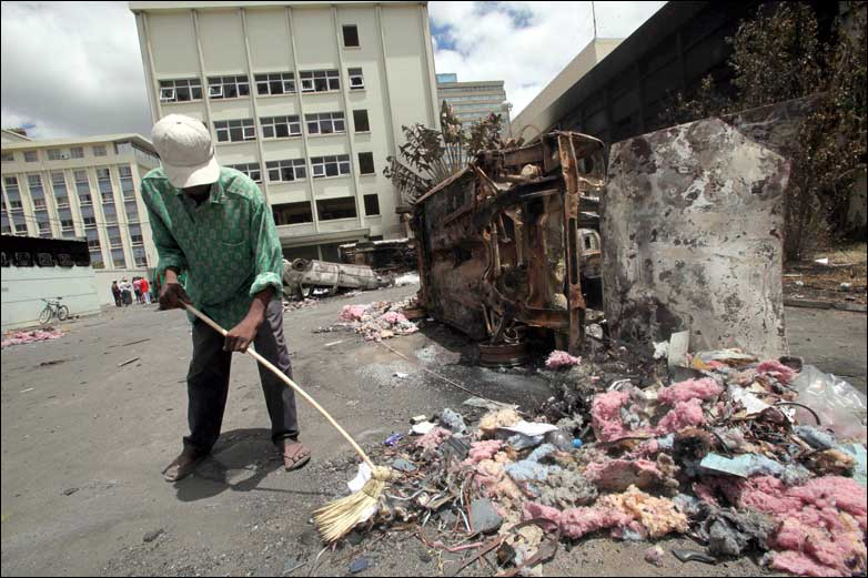 A man sweeps debris from a street
