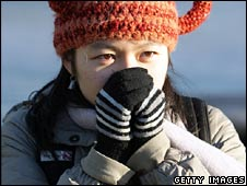 Woman keeping warm in cold weather, London Jan 2009