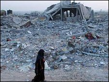 A woman walks through the rubble of homes destroyed during the Israeli offensive in Gaza. Photo: 20 January 2009