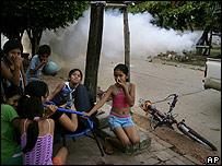 Niños se protegen mientras las autoridades fumigan las calles en Santa Cruz
