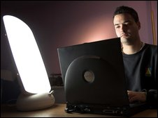 Man working at laptop with SAD lamp