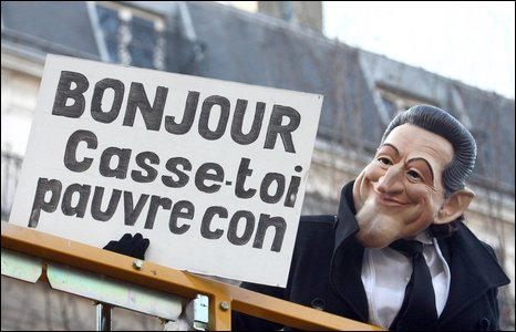 A demonstrator in Paris wears a Sarkozy mask