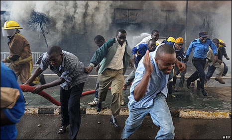 Onlookers and emergency workers flee after a loud blast is heard from inside the burning supermarket in Nairobi on 28/1/08