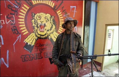 Soldier in front of Tamil Tiger logo in Mullaitivu