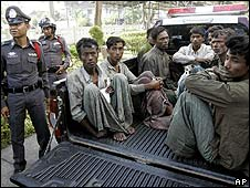 Rohingya migrants look out from a police vehicle in Thailand