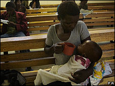 Woman feeds a child at the Budiriro Cholera clinic in Harare, Zimbabwe, in December 2008