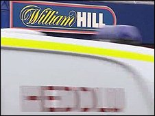 Police vehicle passing William Hill in Albany Road, Roath, Cardiff