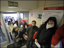 People queue as they wait for a government job centre to open in Madrid