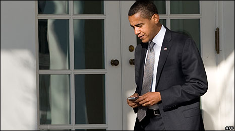 Barack Obama uses a handheld mobile device in the grounds of the White House, 29 January 2009