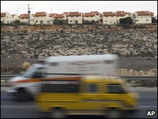 Cars drive past the Jewish settlement of Ofra in the West Bank