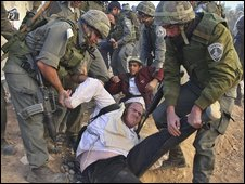 Israeli police officers and soldiers remove Jewish settlers during the evacuation of a disputed house in the West Bank city of Hebron on 4 December 2008