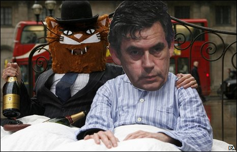 Protesters dressed as a City fat cat and Gordon Brown in bed together