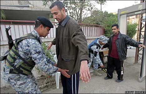 Iraqi policemen search voters outside a polling station in Baghdad