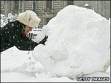 Woman pushes a snowball