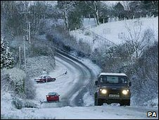 Cars travel along snowy road