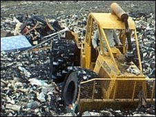 Yellow digger on rubbish dump