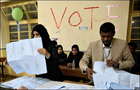 Iraqi electoral workers empty ballot boxes
