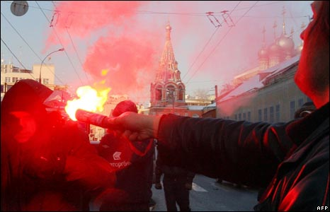 A Russian opposition supporter (R) uses a flare during a fight with a pro-government supporter (L) at an anti-government rally in central Moscow