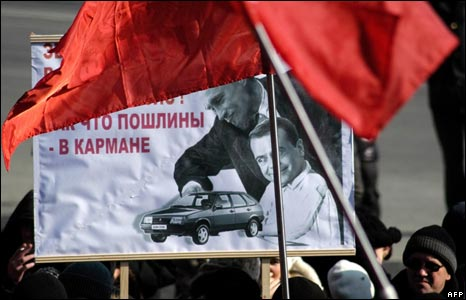 Russian Communist Party supporters hold a poster featuring Russian President Dmitry Medvedev and Prime Minister Vladimir Putin during pro-Communist rally in the centre of Vladivostok