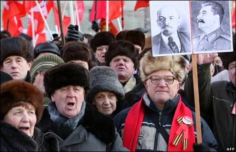 A Russian Communist Party supporter holds a pictures of late Soviet leaders Vladimir Lenin (L) and Josef Stalin during an anti-government rally in the centre of Moscow