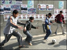 children play soccer close to a blast wall plastered with election posters in central Baghdad on Saturday