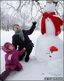 A mother and daughter build a snow man in Kensington Gardens , London