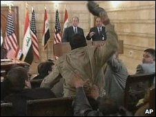 An image from APTN video showing a man throwing a shoe at US President George W Bush